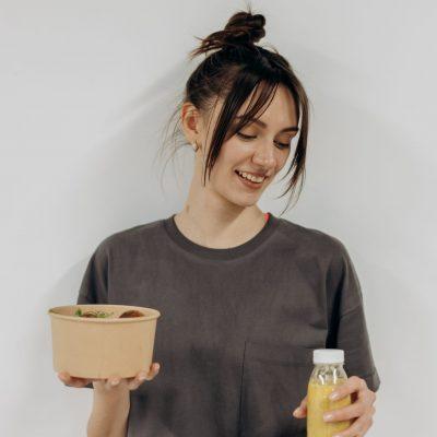 בחורה מחזיקה משקה ומאכל טבעוני